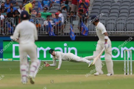 India's Virat Kohli, left, and Ajinkya Rahane look on as Australia's Peter Handscomb dives to stop the ball during play in the second cricket test between Australia and India in Perth, Australia