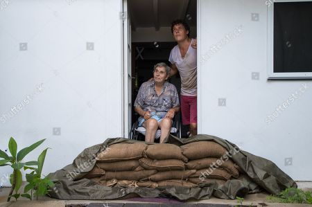 Stock Image of Parramatta Park resident John Irving (L) and his son Steve Irving (R) look at the sky from their sandbagged doorway in Cairns, Queensland, Australia, 15 December 2018. Flash flooding warnings have been issued for parts of Queensland as Cyclone Owen makes landfall in the north-eastern state.