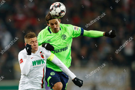 Augsburg's Alfred Finnbogason, left, and Schalke's Benjamin Stambouli challenge for the ball during the German Bundesliga soccer match between FC Augsburg and FC Schalke 04 in Augsburg, Germany