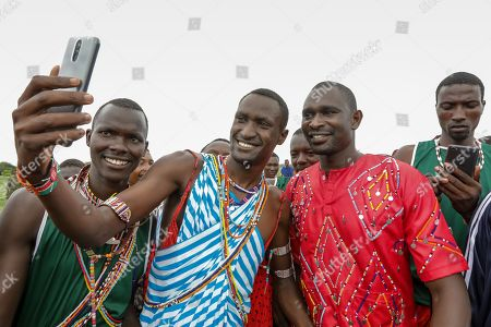 Young Maasai moran athletes take a selfie picture with Kenya's 800m gold medalist David Rudisha (2-R), during competitions at the Maasai Olympics 2018, held in Kimana village near the border with Tanzania, adjacent to the Amboseli National Park in Kenya, 15 December 2018. Hundreds of young Maasai men representing four manyattas (villages) competed in six games to win medals, cash prizes or a breeding bull. The Maasai Olympics, first held in 2012, was organized by Maasai leaders and the wildlife conservation group 'Big Life Foundation' to stop the killings of lions and other wild animals. The event aims to change the mindset of young Maasai men whose traditional lion hunting has been an important coming-of-age ritual.