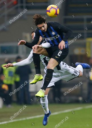 Inter Milan's Sime Vrsaljko, top, and Udinese's Rolando Mandragora vie for the ball during an Italian Serie A soccer match between Inter Milan and Udinese, at the San Siro stadium in Milan, Italy