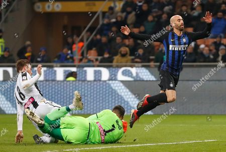 Udinese goalkeeper Juan Musso, saves on Inter Milan's Borja Valero, during an Italian Serie A soccer match between Inter Milan and Udinese, at the San Siro stadium in Milan, Italy