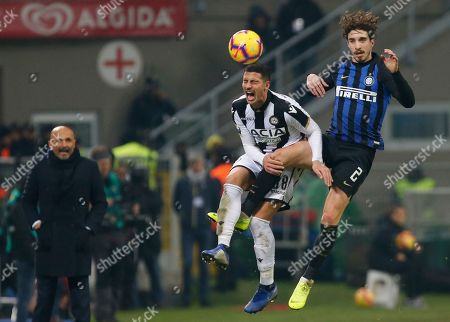 Inter Milan's Sime Vrsaljko, right, and Udinese's Rolando Mandragora vie for the ball as Inter Milan coach Luciano Spalletti looks on during an Italian Serie A soccer match between Inter Milan and Udinese, at the San Siro stadium in Milan, Italy