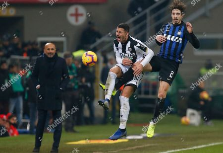 Stock Image of Inter Milan's Sime Vrsaljko, right, and Udinese's Rolando Mandragora vie for the ball as Inter Milan coach Luciano Spalletti looks on during an Italian Serie A soccer match between Inter Milan and Udinese, at the San Siro stadium in Milan, Italy