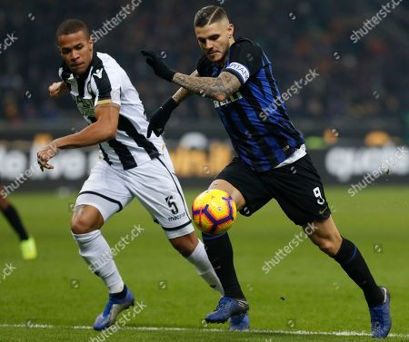 Inter Milan's Mauro Icardi and Udinese's William Troost Ekong, left, vie for the ball during an Italian Serie A soccer match between Inter Milan and Udinese, at the San Siro stadium in Milan, Italy