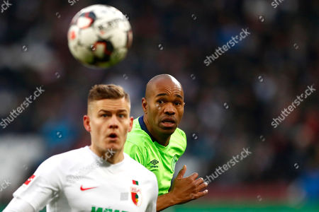 Schalke's Naldo, background, watches the ball behind Augsburg's Alfred Finnbogason during the German Bundesliga soccer match between FC Augsburg and FC Schalke 04 in Augsburg, Germany