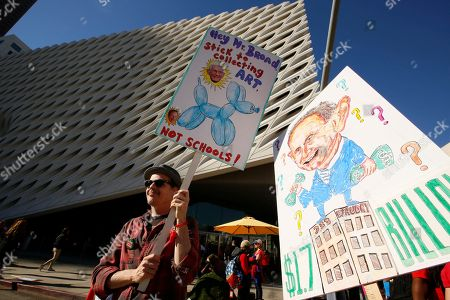 United Teachers Los Angeles member, art teacher Bradley Greer, left, shows cases his artwork at a union rally next to the Broad Museum in downtown Los Angeles . The union contends that the district is hoarding a huge financial reserve that could be used to pay teachers more and improve conditions for students. Union leaders also criticized a plan to reorganize the district by dividing it into 32 networks. Saturday's march ended at the Broad Museum to highlight the role billionaires like Eli Broad have by funding the corporate charter industry and privatization efforts. The drawing at right depicts LAUSD Superintendent Austin Beutner, a former investment banker