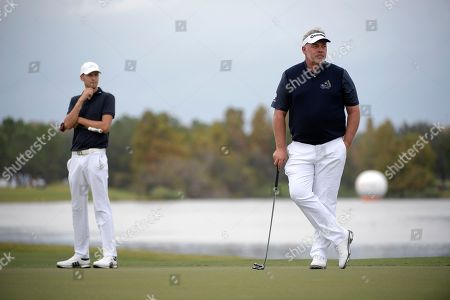 Stock Image of Darren Clarke, right, and his son, Tyrone Clarke, wait to putt on the 18th green during the first round of the Father Son Challenge golf tournament, in Orlando, Fla
