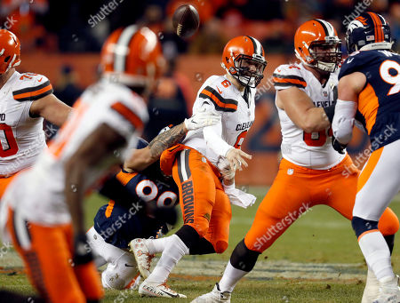 Stock Photo of Denver Broncos defensive end Adam Gotsis, rear, forces Cleveland Browns quarterback Baker Mayfield (6) to fumble the football during the second half of an NFL football game, in Denver. The Broncos recovered the ball