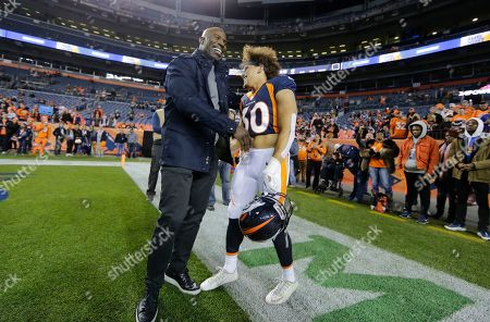 Former Denver Broncos running back Terrell Davis greets current Broncos running back Phillip Lindsay (30) prior to an NFL football game against the Cleveland Browns, in Denver
