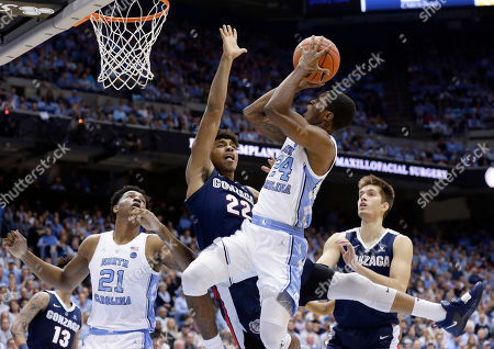Jeremy Jones, Kenny Williams, Sterling Manley, Filip Petrusev. North Carolina's Kenny Williams (24) shoots while Gonzaga's Jeremy Jones (22) and Filip Petrusev, right, defend during the first half of an NCAA college basketball game in Chapel Hill, N.C., . North Carolina's Sterling Manley (21) looks on at left