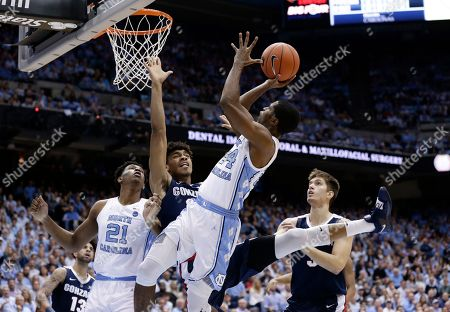 North Carolina's Kenny Williams (24) shoots while Gonzaga's Jeremy Jones (22) and Filip Petrusev, right, defend during the first half of an NCAA college basketball game in Chapel Hill, N.C., . North Carolina's Sterling Manley (21) looks on at left