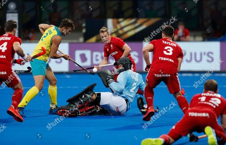 Australia's Tom Craig, second left, lifts the ball to score a goal during the Men's Hockey World Cup bronze medal match between Australia and England at Kalinga Stadium in Bhubaneswar, India
