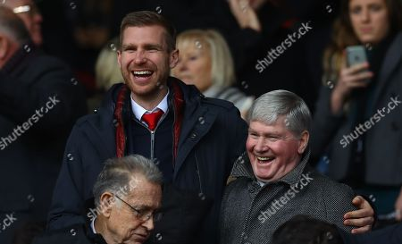 Stock Picture of Per Mertesacker and Pat Rice embrace in the stands