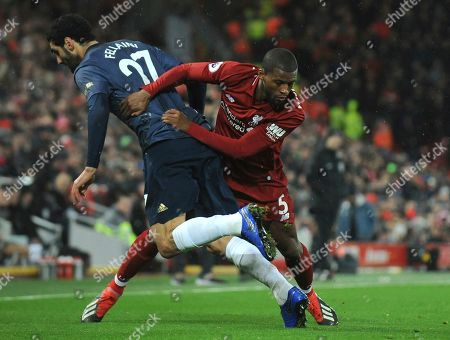 Manchester United's Marouane Fellaini, left, and Liverpool's Georginio Wijnaldum challenge for the ball during the English Premier League soccer match between Liverpool and Manchester United at Anfield in Liverpool, England
