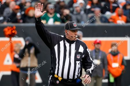 Official Rich Hall (49) gestures in the second half of an NFL football game between the Cincinnati Bengals and the Oakland Raiders, in Cincinnati