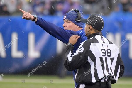 New York Giants head coach Pat Shurmur, back, talks to head linesman Greg Bradley (98) during the first half of an NFL football game against the Tennessee Titans, in East Rutherford, N.J