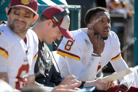 Washington Redskins quarterback Mark Sanchez (6) watches from the bench with passing game coordinator Kevin O'Connell, center, and quarterback Josh Johnson (8) during the first half of an NFL football game against the Jacksonville Jaguars, in Jacksonville, Fla