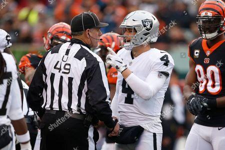 Oakland Raiders quarterback Derek Carr (4) speaks with umpire Rich Hall (49) in the second half of an NFL football game against the Cincinnati Bengals, in Cincinnati