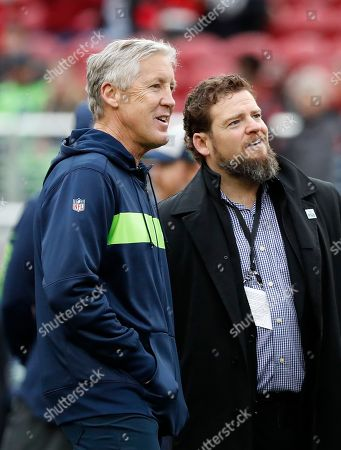 Seattle Seahawks head coach Pete Carroll talks with general manager John Schneider before an NFL football game against the San Francisco 49ers in Santa Clara, Calif