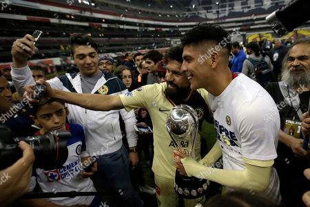 America's Oribe Peralta and Edson Alvarez pose for a photo with the trophy as they celebrate defeating Cruz Azul in the final Mexico soccer league championship match at Azteca stadium in Mexico City