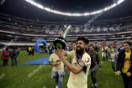 America's Oribe Peralta holds the trophy after defeating Cruz Azul in the final Mexico soccer league championship match at Azteca stadium in Mexico City