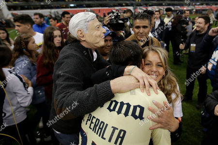 A man wearing a mask of Mexico's President Andres Manuel Lopez Obrador celebrates with America's Oribe Peralta defeating Cruz Azul in the final Mexico soccer league championship match at Azteca stadium in Mexico City