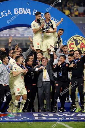 Oribe Peralta (L) and Paul Aguilar (R) of Club America lift the trophy after beating Cruz Azul during the Apertura Tournament finals second leg soccer match between Cruz Azul and Club America at the Azteca Stadium in Mexico City, Mexico, 16 December 2018.
