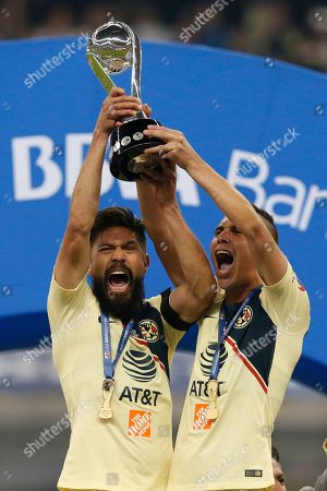 America's Paul Aguilar, left, and Oribe Peralta hold their team's trophy after defeating Cruz Azul in the final Mexico soccer league championship match at Azteca stadium in Mexico City