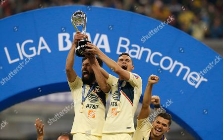 America's Paul Aguilar, center left, and Oribe Peralta hold their team's trophy after defeating Cruz Azul in the final Mexico soccer league championship match at Azteca stadium in Mexico City