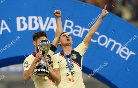 America's Paul Aguilar, right, and Oribe Peralta hold their team's trophy after defeating Cruz Azul in the final Mexico soccer league championship match at Azteca stadium in Mexico City