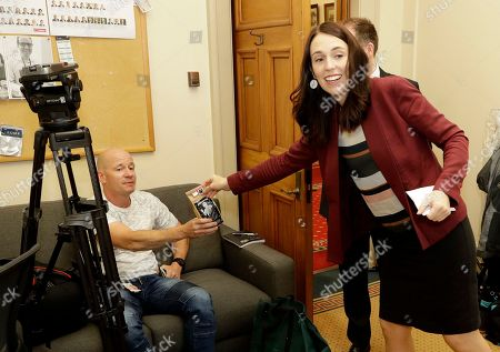 New Zealand Prime Minister Jacinda Arden, right, hands out bags of coffee to the media as a Christmas present in Parliament in Wellington, New Zealand, . Prime Minister Ardern said that six months after giving birth, she's looking forward to spending more time with her daughter Neve over the Christmas break and thanking everybody who's helped her juggle responsibilities