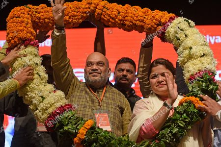 President of Bhartiya Janta Party Yuva Morcha and Member of Parliament Poonam Mahajan and BJP President Amit Shah are garlanded on the second day of the BJP national workshop, at Civic Centre