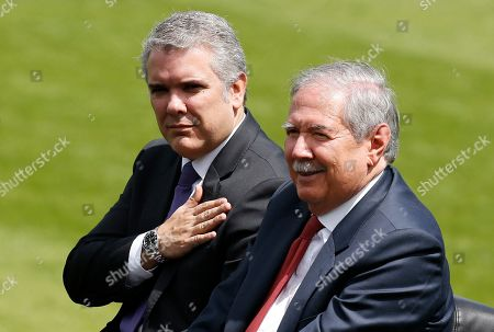 Colombia's President Ivan Duque places his hand over his chest as he reviews the troops with Defense Minister Guillermo Botero during a swearing-in ceremony for the new military and police commanders, in Bogota, Colombia