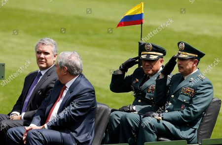 President Ivan Duque, left, Defense Minister Guillermo Botero, second from left, Armed Forces Commander Gen. Luis Fernando Navarro, second from right, and Army Commander Gen. Nicacio Martínez, right, review the troops during a swearing-in ceremony for the new military and police commanders, in Bogota, Colombia