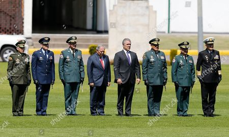 National Police Commander Gen. Oscar Atehortua, from left to right, Air Force Commander Gen. Ramses Rueda, Army Commander Gen. Nicacio Martínez, Defense Minister Guillermo Botero, President Ivan Duque, Armed Forces Commander Gen. Luis Fernando Navarro, Armed Forces Chief of Staff Gen. Juan Bautista Yepes and Navy Commander Vice Admiral Evelio Ramírez, review the troops during a swearing-in ceremony for the new military and police commanders, in Bogota, Colombia