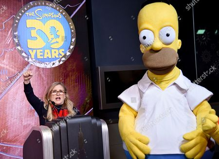 Nancy Cartwright, Homer Simpson. Nancy Cartwright, who voices the character Bart Simpson, left, appears with costumed character Homer Simpson during Fox's 'The Simpsons' 30th anniversary celebration at the Empire State Building, in New York