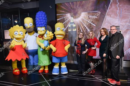 Nancy Cartwright, Pamela Hayden, Stephanie Gillis, Mike Scully. Voice actors Nancy Cartwright, left, and Pamela Hayden, writer Stephanie Gillis and producer Mike Scully pose with costumed characters during Fox's 'The Simpsons' 30th anniversary celebration lighting ceremony at the Empire State Building, in New York