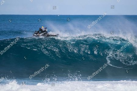 Water Patrol goes over the wave during the action at the Billabong Pipe Masters in memory of Andy Irons at Ehukai Beach Park in Haleiwa, HI