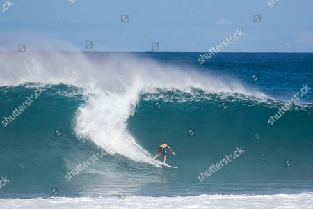 Gabriel Medina bottom turns on a big wave during the Quarterfinals action at the Billabong Pipe Masters in memory of Andy Irons at Ehukai Beach Park in Haleiwa, HI