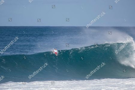 Kelly Slater paddles out and goes over the wave during the action at the Billabong Pipe Masters in memory of Andy Irons at Ehukai Beach Park in Haleiwa, HI