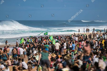 Stock Picture of The crowd was cheering on the surfers in the water during the action at the Billabong Pipe Masters in memory of Andy Irons at Ehukai Beach Park in Haleiwa, HI