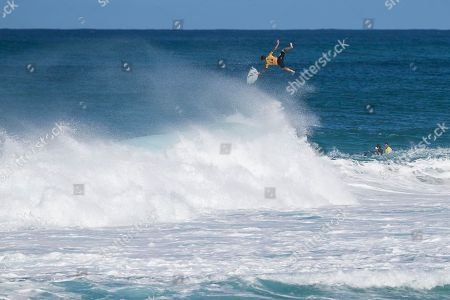 Stock Photo of Gabriel Medina jumps off his board mid flight after coming out of a barrel during the Quarterfinals action at the Billabong Pipe Masters in memory of Andy Irons at Ehukai Beach Park in Haleiwa, HI