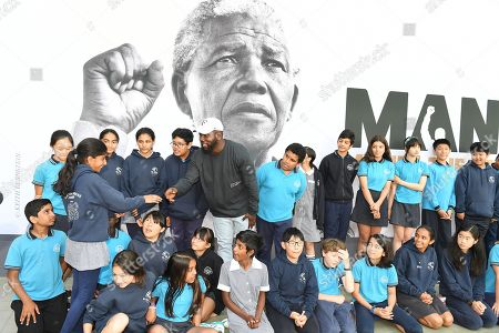 Stock Photo of Kweku Mandela (C), the grandson of late South African President Nelson Mandela, interacts with school students at the Melbourne Museum in Melbourne, Australia, 18 December 2018. Kweku Mandela visited the 'Mandela: My Life' Exhibition for the first time and guided a group of Year 6 students from Carlton Gardens Primary School through the exhibition.