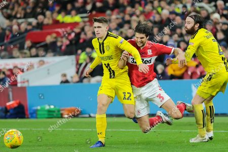 Middlesbrough defender George Friend (3) goes to ground under pressure from Burton Albion midfielder Ben Fox (12) and Burton Albion defender John Brayford (2) during the quarter final of the EFL Cup match between Middlesbrough and Burton Albion at the Riverside Stadium, Middlesbrough