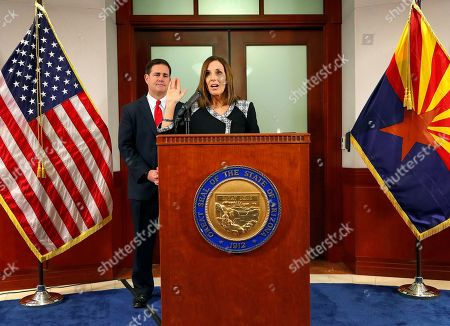 U.S. Rep. Martha McSally, R-Ariz., speaks, during a news conference, at the Capitol in Phoenix, after Arizona Gov. Doug Ducey, rear, announced his decision to replace U.S. Sen. Jon Kyl, R-Ariz. with McSally in the U.S. Senate seat that belonged to Sen. John McCain. McSally will take over after Kyl's resignation becomes effective Dec. 31
