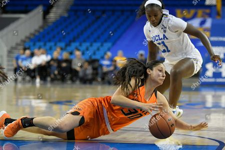 UCLA forward Michaela Onyenwere (21) watches Oklahoma State guard Maria Castro (30) dive for the ball in the second half during an NCAA college womens basketball game, in Los Angeles. UCLA won 71-59