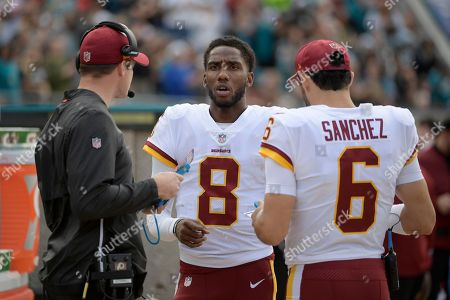 Stock Image of Washington Redskins passing game coordinator Kevin O'Connell, left, talks with quarterback Josh Johnson (8) and quarterback Mark Sanchez (6) on the sideline during the first half of an NFL football game against the Jacksonville Jaguars, in Jacksonville, Fla