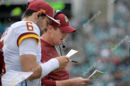 Washington Redskins quarterback Mark Sanchez and head coach Jay Gruden watch from the sideline during the first half of an NFL football game against the Jacksonville Jaguars, in Jacksonville, Fla