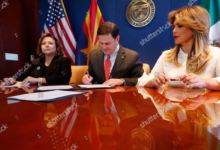 Arizona Gov. Doug Ducey, center, signs an agreement to a cross-border plan to provide natural gas to Asia as New Mexico Gov. Susana Martinez, left, and Gov. Claudia Pavlovich of Mexico's Sonora state watch, at the Capitol in Phoenix